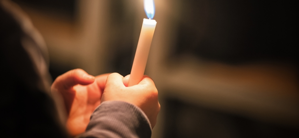 white hands holding lit candle in dark