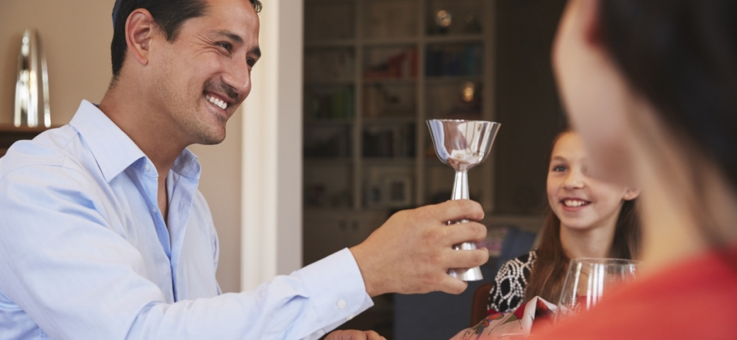 A person in a blue button down with short brown hair and a faint brown mustache holds up a kiddush cup with a smile.