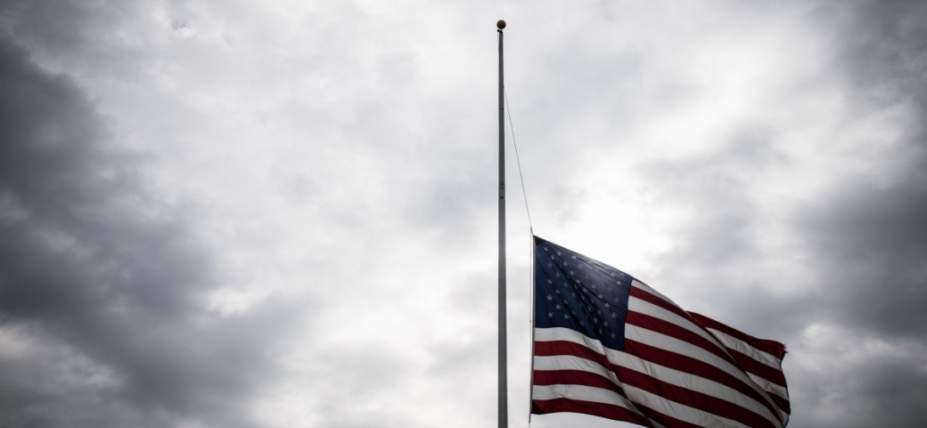 american flag at half mast with gray cloudy sky in the background