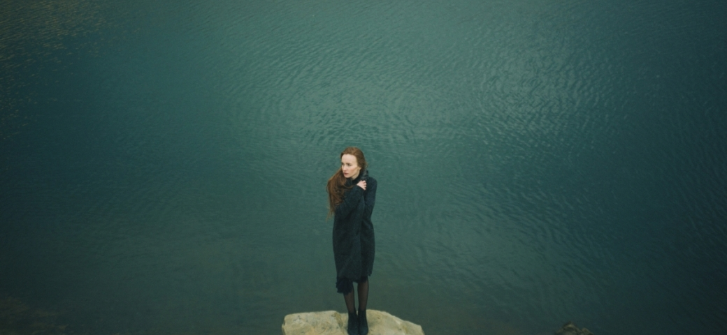 woman with red and hair and light skin standing on large rock shown from far away with ocean behind her. her head is turned to one side and she's wearing all black with her hand in a fist at her chest.