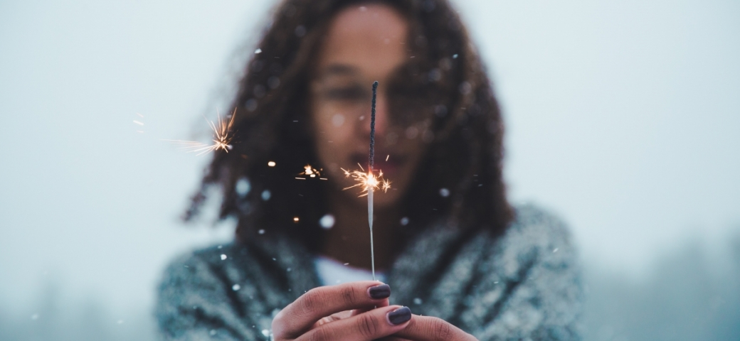 close up of brown-skinned woman's hands holding lit sparkler, her face blurred in the background, curly brown hair swept to the side by breeze