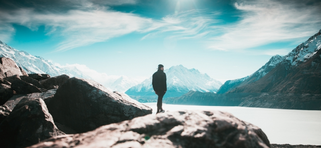 sunlit mountains with man in black jacket standing in the middle