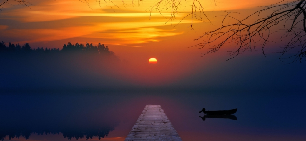 sunset over lake with pier and small boat