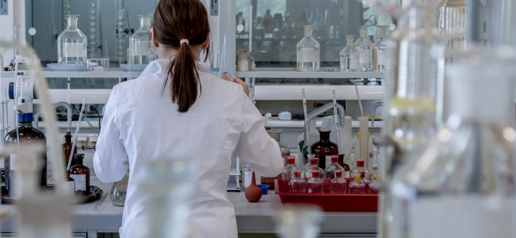 a person with brown hair pulled back in a low ponytail is wearing a labcoat and is pictured from the back in front of a table in a lab filled with bottles and vials