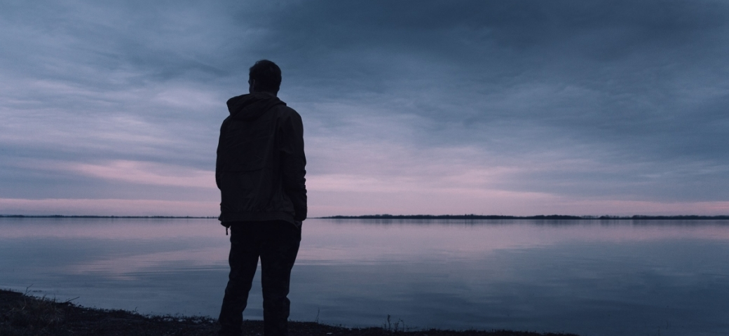 silhouette of man looking out at dark grey pinkish sky and water