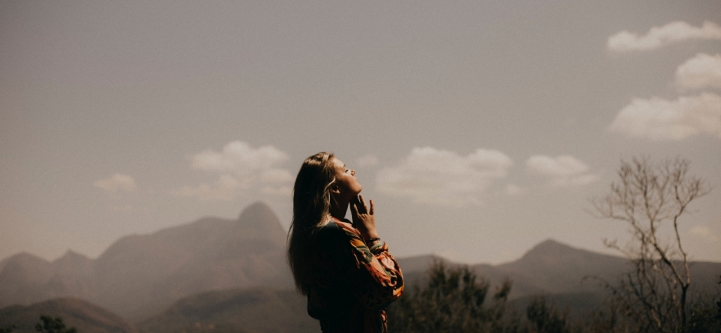 woman with blonde hair, eyes closed and hands together, looking up to sky with sunlight, clouds, mountains