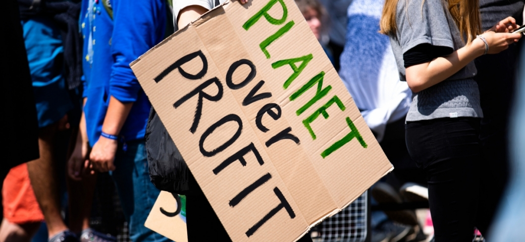 a crowd of people are in the background. In the center is a person hold a cardboard sign thats says PLANET in green paint and OVER PROFIT in black paint