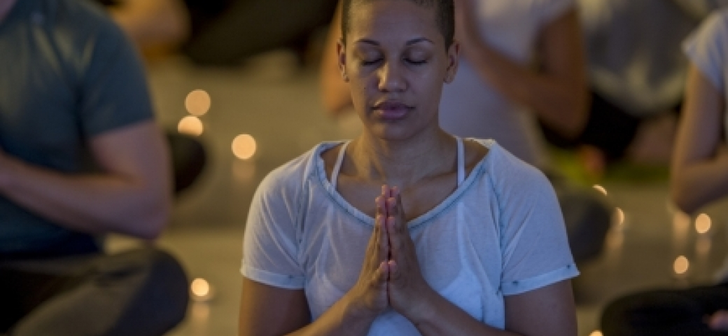woman meditating in dim light, with other meditators and candles in background