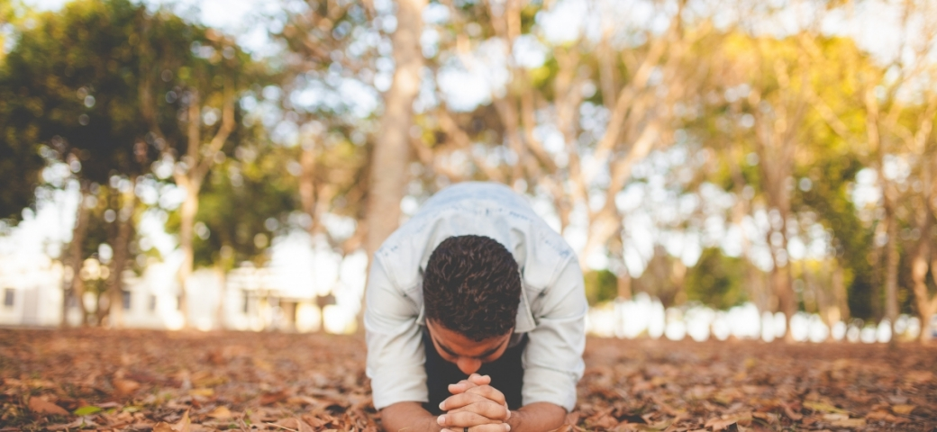light-skinned man with brown hair kneeling in prayer with hands clasped in a forest