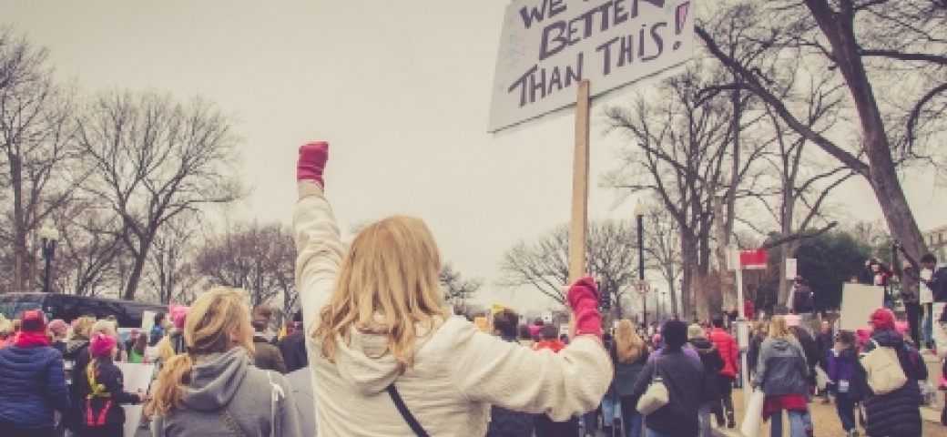 """protest with closeup of white woman holding a sign that reads, """"we are better than this"""""""