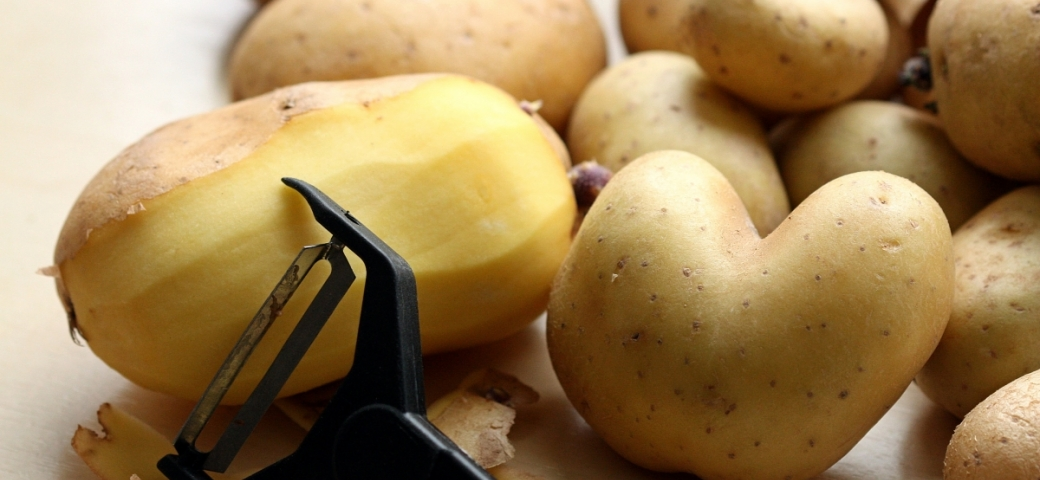 a bunch of yellow potatoes are pictured. In the right side of the picture is one partially peeled and in front of it rests a black peeler.