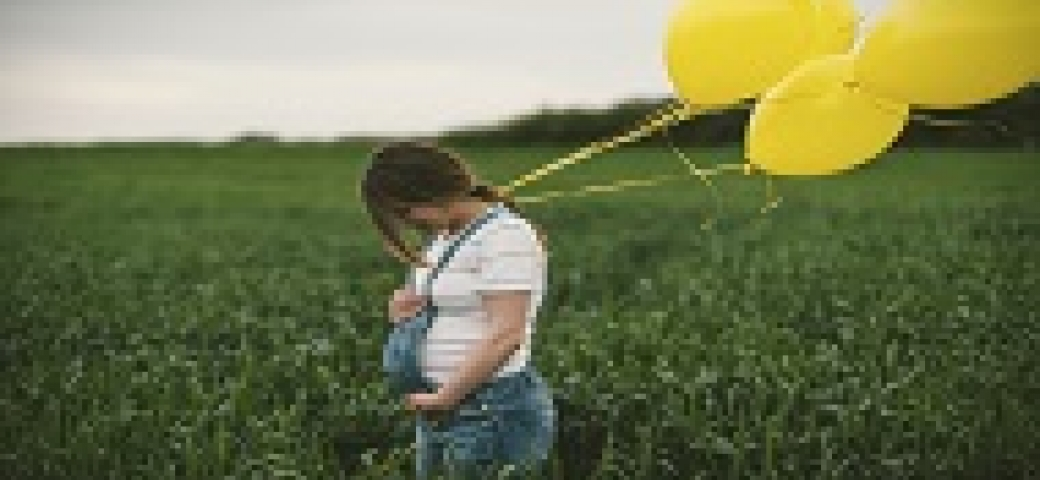 pregnant woman standing in field cradling belly holding balloons