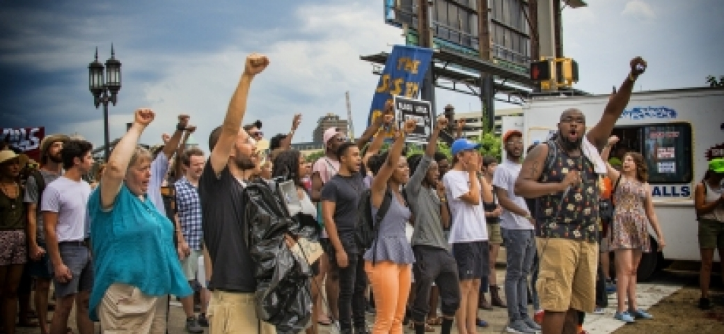 multiracial group of black lives matter protesters with arms raised to the air