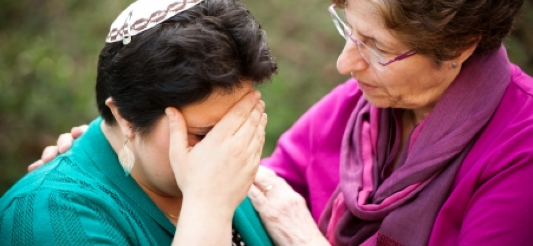 older woman comforting younger woman wearing kippah with hand over face