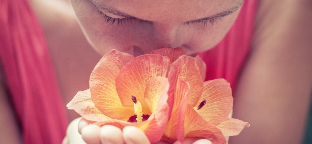 light-skinned woman smelling yellow-coral colored flower