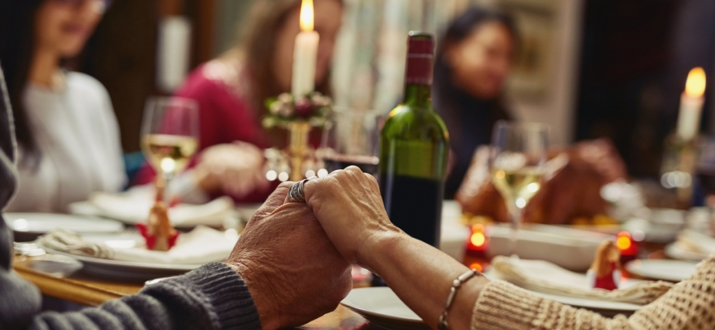shabbat dinner table with candles wine and people sitting around table with close up of two people holding hands at the table