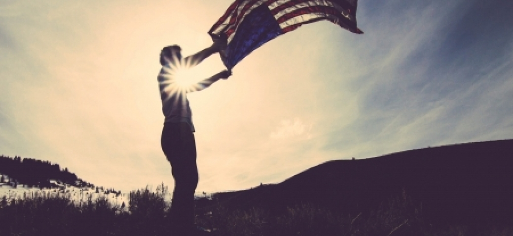 person holding american flag up in the wind in the sunlight