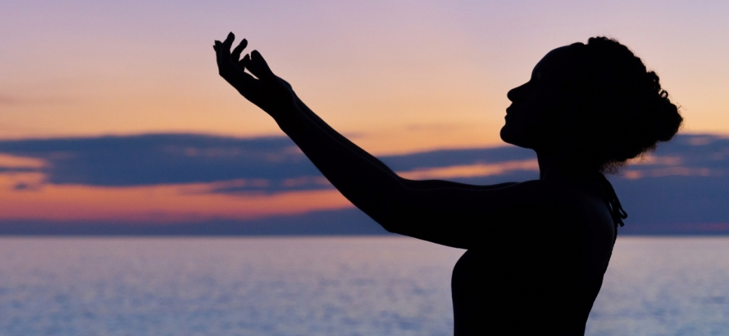 silhouette of woman holding hands open to sky, sea and clouds in background