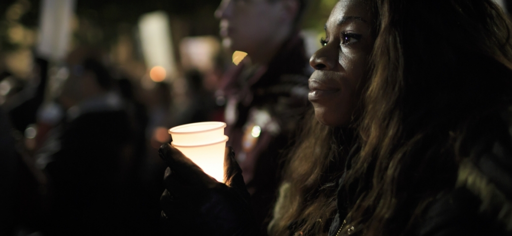 a black woman with long dark hair is holding a cup lit by a candle inside of it. In the background there are other people with candles.