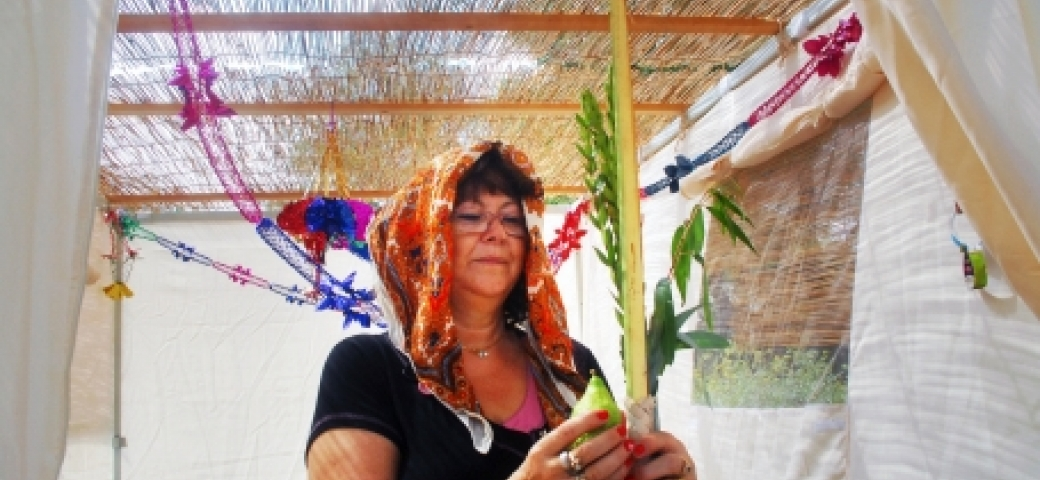 woman with head covered shaking lulav in sukkah