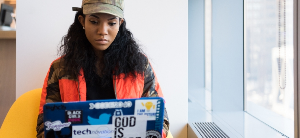 """A black woman with long dark hair is sitting on a yellow chair with their laptop on their lap. They are very focused on the screen. On the laptop are several stickers, including one thats says """"God is hope""""."""