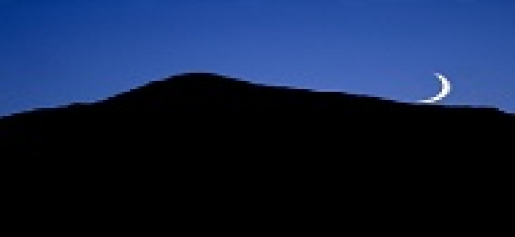 crescent moon rising over the silhouette of a mountain