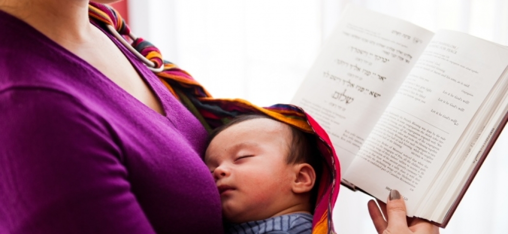 Mother holding siddur with baby in sling