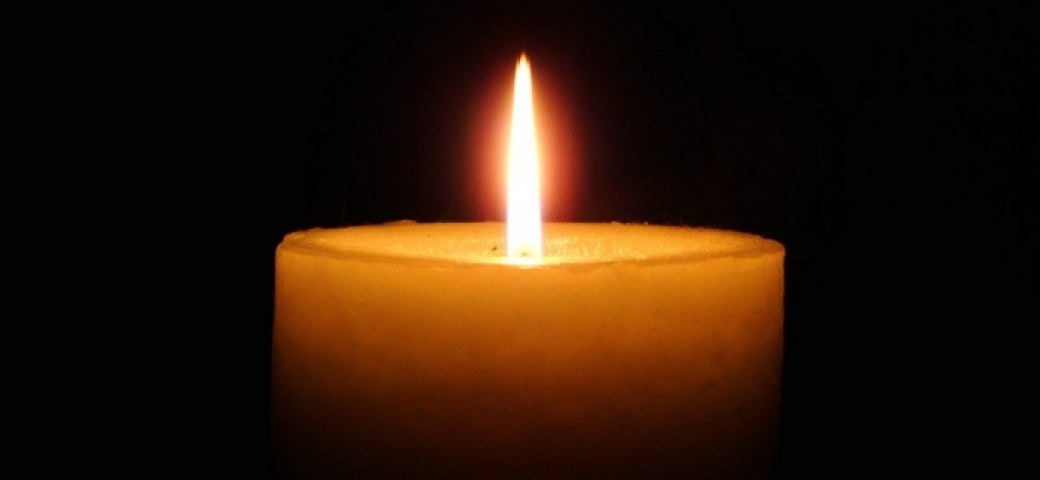 Single candle lit against a black background