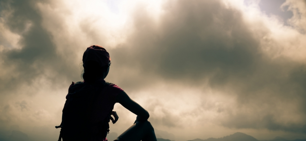 silhouette of a person who has been hiking, sitting on the ground looking at the view