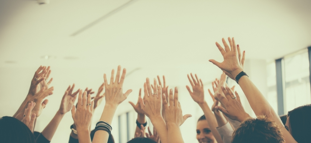 group of people with hands up in the air smiling