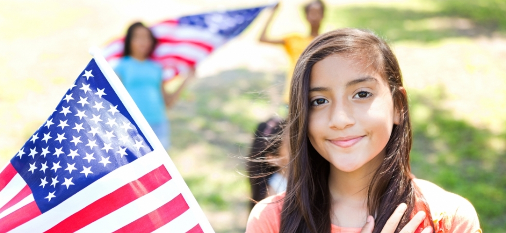 brown girl with hand on heart next to american flag