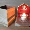 yizkor box and candle with red background with a trellis background