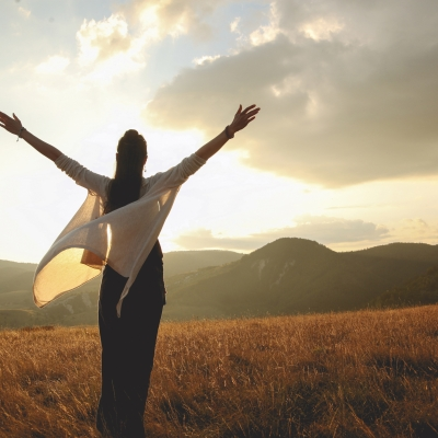 woman standing, facing the sun and mountains with arms raised