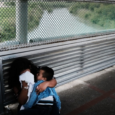 Photo of mother covering her face with a cloth, clutching a child, next to a fence with a river in the background