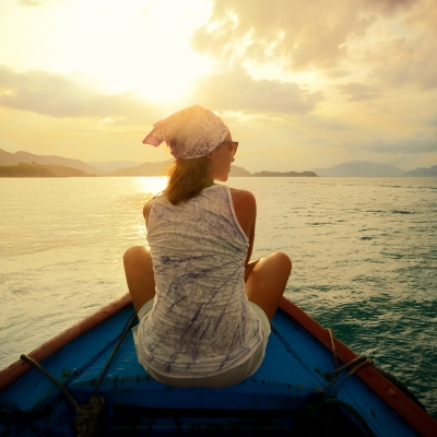 woman sitting on boat in the water with sun shining