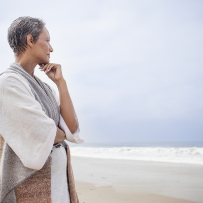 older woman looking contemplatively at the sea