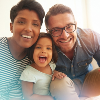 two parents sandwich their child. The parent on the left is wearing a striped shirt and has short brown hair and dark skin. The parent on the right has on a blue denim button down and khaki pants, is wearing glasses, and has short brown hair and fair skin. The child has a big smile on their face with straight short brown hair, dark skin, and a green shirt on.