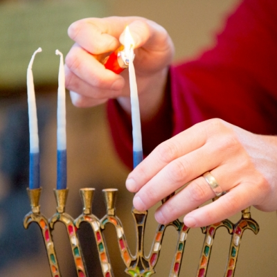 close up of person lighting the shamash of a menorah with two candles
