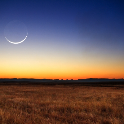 crescent moon over sky with changing colors, orange yellow blue
