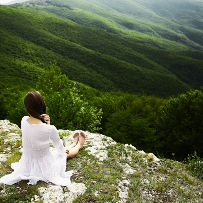 girl in white dress sitting at edge of mountain looking out to green expanse