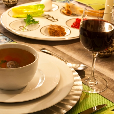 A place setting with a full glass of red wine and a bowl of matzah ball soup is pictured. In the background we see a seder plate filled