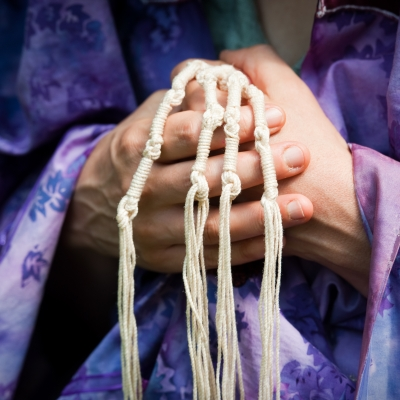 close up of older person's hands holding the four corners of a purple tallit, gathering the tzitzit (strings) together