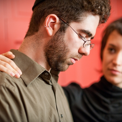 man looking down and sad with woman's hand on his shoulder. woman looks concerned and supportive.