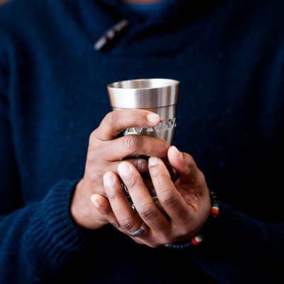 close up of black person's hands holding silver kiddush cup