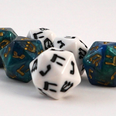 Six 20 sided dreidels are pictured. Three are turquoise with gold lettering and three are white with black lettering. The one in the front is white and you can see the letter nun shin and khet