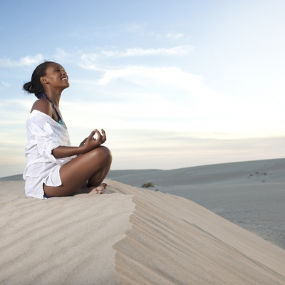 black woman sitting in meditation smiling up at the sky in the desert