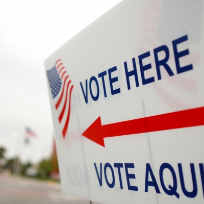 sign that reads vote here with large arrow