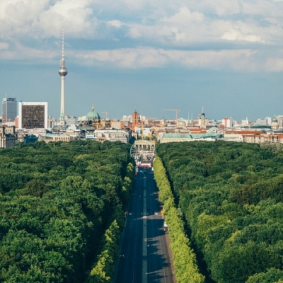 An aerial view of Berlin with lots of green trees in the forefront of the image and buildings in the back.