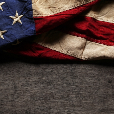 a folded american flag takes up half of the photo with the blue background and white embroidered stars on the left of the image and alternating red and white stripes on the right side. The flag is worn and resting on a grey surface