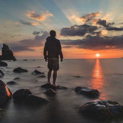 person standing on a rock at the edge of the ocean looking at sunset
